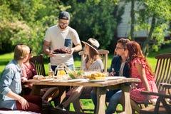 Amis heureux dînant à la réception en plein air d'été Photos stock