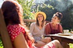 Amis heureux dînant au jardin d'été Image libre de droits