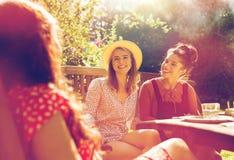Amis heureux dînant au jardin d'été Photo libre de droits