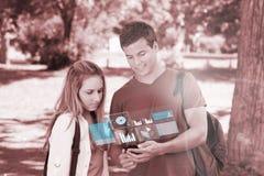 Amis heureux d'université à l'aide du téléphone numérique Images stock