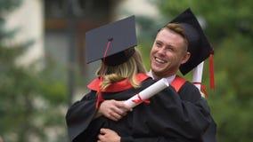 Amis heureux d'université étreignant chaudement, félicitations sur la cérémonie  clips vidéos