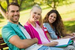 Amis heureux d'université s'asseyant sur le banc de campus Photographie stock
