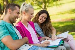Amis heureux d'université s'asseyant sur le banc de campus Photographie stock libre de droits
