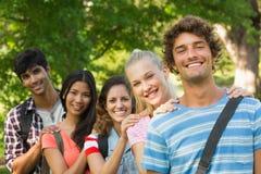 Amis heureux d'université se tenant dans la rangée au campus Photographie stock