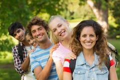 Amis heureux d'université se tenant dans la rangée au campus Image libre de droits