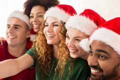 Amis heureux dans des chapeaux de Santa à la fête de Noël Images stock