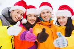 Amis heureux dans des chapeaux de Santa et des costumes de ski dehors Photographie stock libre de droits