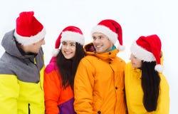 Amis heureux dans des chapeaux de Santa et des costumes de ski dehors Photographie stock