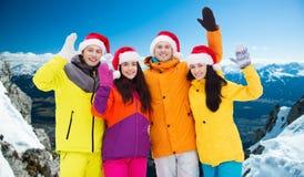 Amis heureux dans des chapeaux de Santa et des costumes de ski dehors Image libre de droits