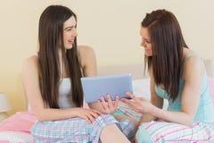 Amis heureux dans des pyjamas parlant sur le lit utilisant un comprimé Images libres de droits