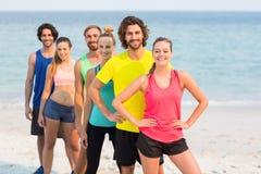 Amis heureux dans l'habillement de sports se tenant à la plage Image stock