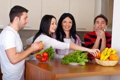 Amis heureux dans la cuisine avec des légumes Photos libres de droits
