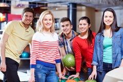 Amis heureux dans le club de bowling Photos stock