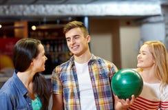 Amis heureux dans le club de bowling Photo stock