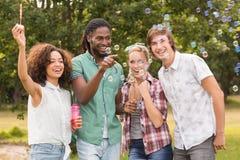 Amis heureux dans les bulles de soufflement de parc Image libre de droits