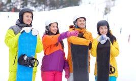 Amis heureux dans les casques avec des surfs des neiges Image libre de droits