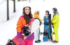 Amis heureux dans les casques avec des surfs des neiges Images stock