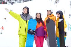 Amis heureux dans les casques avec des surfs des neiges Image stock