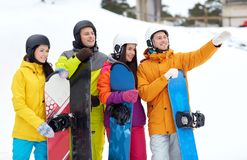 Amis heureux dans les casques avec des surfs des neiges Images libres de droits