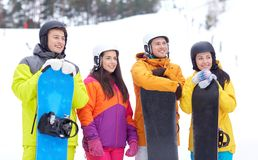 Amis heureux dans les casques avec des surfs des neiges Photographie stock