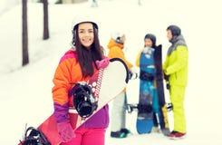 Amis heureux dans les casques avec des surfs des neiges Photographie stock libre de droits