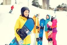 Amis heureux dans les casques avec des surfs des neiges Photo stock