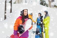 Amis heureux dans les casques avec des surfs des neiges Photos libres de droits