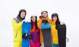 Amis heureux dans les casques avec des surfs des neiges dehors Photos libres de droits