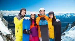 Amis heureux dans les casques avec des surfs des neiges dehors Photographie stock