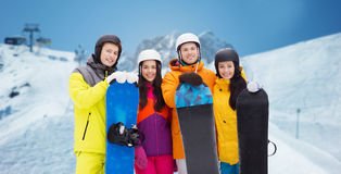 Amis heureux dans les casques avec des surfs des neiges dehors Image libre de droits