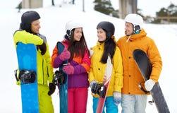 Amis heureux dans les casques avec parler de surfs des neiges Image libre de droits