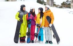 Amis heureux dans les casques avec parler de surfs des neiges Images stock