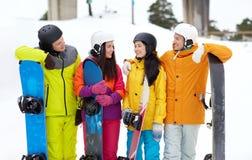 Amis heureux dans les casques avec parler de surfs des neiges Photographie stock libre de droits