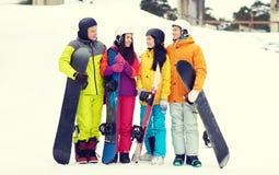 Amis heureux dans les casques avec parler de surfs des neiges Photo stock