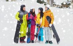 Amis heureux dans les casques avec parler de surfs des neiges Photos stock