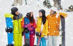 Amis heureux dans les casques avec parler de surfs des neiges Photos libres de droits