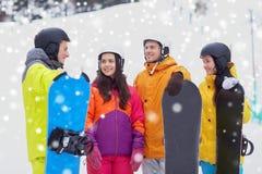 Amis heureux dans les casques avec parler de surfs des neiges Images libres de droits