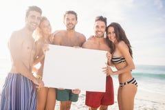 Amis heureux dans les vêtements de bain tenant un signe Photographie stock