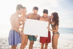 Amis heureux dans les vêtements de bain tenant un signe Image libre de droits