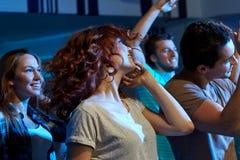 Amis heureux dansant à la boîte de nuit Photo stock