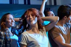 Amis heureux dansant à la boîte de nuit Photographie stock