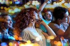 Amis heureux dansant à la boîte de nuit Photographie stock libre de droits
