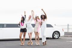 Amis heureux dansant devant une limousine Image libre de droits