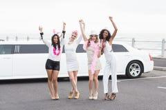 Amis heureux dansant devant une limousine Photographie stock libre de droits