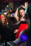 Amis heureux dansant par la cabine du DJ Photographie stock libre de droits