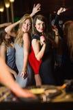 Amis heureux dansant par la cabine du DJ Image stock