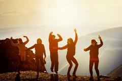Amis heureux dansant sur la montagne de coucher du soleil Images stock