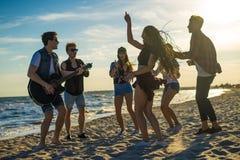 Amis heureux dansant sur la plage Les hommes joue la guitare Image libre de droits