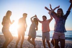 Amis heureux dansant sur le sable Image libre de droits