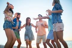 Amis heureux dansant sur le sable Images stock